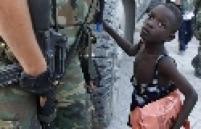 Uma criança pede ajuda a um soldado, em Porto Príncipe
