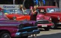 Apesar da reaproximação, Washington mantém o embargo econômico contra Cuba, o que torna mais difícil para empresas europeias com negócios nos EUA operarem na ilha. Na imagem, turista tira foto ao lado de carro clássico em Havana
