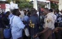 Segurança haitiano tenta manter a ordem onde pessoas esperam em fila por gasolina