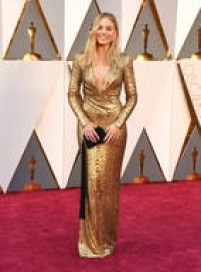 A atriz Margot Robbie é uma das mais modernas da noite, com um look dourado da marca DVF e cabelos naturais.
