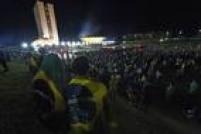 Pessoas vestem a bandeira do Brasil em frente ao Congresso Nacional