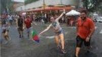 Sob forte chuva, pessoas brincam entre as ruas Martim Francisco e Imaculada Conceição, na Santa Cecília
