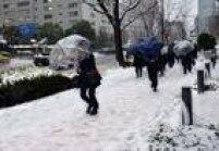 Pedestres enfrentam os fortes ventos e a neve nas ruas de Tóquio
