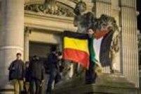 Homem muçulmano ergue bandeiras da Bélgica e da Palestina durante homenagens a mortos em Bruxelas