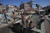Crianças brincam no Rio em uma piscina sem sistema de drenagem e limpeza de água