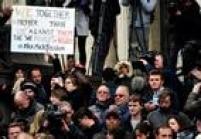"""Homem segura cartaz em que se lê """"Nós juntos é melhor do que nós contra eles"""" durante minuto de silêncio"""