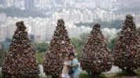 Casal faz foto selfie em frente de árvores cobertas de cadeados no topo do monte Namsan em Seul. Foto:Kim Hong-Ji/Reuters