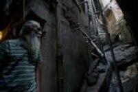 José Martins, de 68 anos, próximo a uma vala ao ar livre na Favela da Rocinha