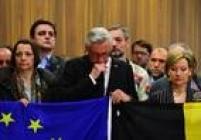 Membros da Comissão Europeia seguram bandeiras da União Europeia e da Bélgica duranteminuto de silêncio