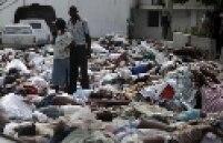 Duas pessoas procuram por vítimas entre centenas de corpos, em Porto Príncipe