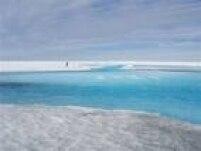 Fluxo de água derretida corre pela superfície de gelo em direção a um lago na Groenlândia