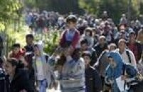 Refugiado carrega criança nas costas enquanto caminha em direção aHegyeshalom
