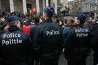 Oficiais fazem a segurança da Praça da Bolsa, em Bruxelas, enquanto moradores observam um minuto de silêncio em homenagem às vítimas