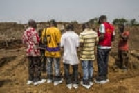 Uma família veste calçados de proteção ao rezar no túmulo de um parente que morreu por causa de uma doença relacionada ao Ebola