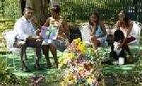 """O presidente Obama (E) e a primeira-dama Michelle leem o livro """"Chicka Chicka Boom Boom"""" para crianças durante a Corrida Anual dos Ovos, realizada nos jardins da Casa Branca, em 2011. Sasha e Malia acompanham a leitura ao lado do cachorro da família, Bo"""