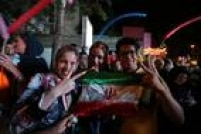 """Mulheres iranianas exibem a bandeira do país e fazemo """"V"""" da vitória em comemorações na capital Teerã após acordo nuclear com potências"""
