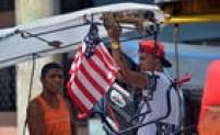 Dois motoristas de bicitáxi (meio de transporte pago e realizado por meio de bicicletas) conversam ao lado de bandeira americana poucos dias antes da chegada de Obama