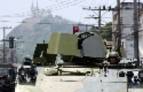 Tanques são desembarcados na entrada na favela, onde traficantes armados resistem à operação