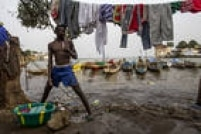 Um morador lava roupas em um cais onde os barcos de pesca ociosos estão parados