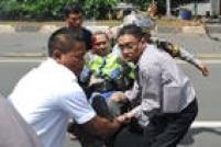 Policial ferido é carregado por civis perto do local de uma explosão em Jacarta, na capital da Indonéia