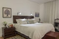 No quarto principal a cama tem cabeceira de madeira maciça