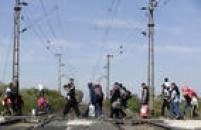 Imigrantes caminham sobtrilhos detrem enquanto seguem em direção à fronteira com a Áustria