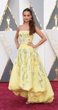 """Primeiro nome de peso a cruzar o red carpet do Oscar 2016, Alicia Vikander surgiu com um vestido amarelo da Louis Vuitton, feito sob medida pelo estilista Nicolas Ghesquière. Ela concorre ao prêmio de melhor atriz coadjuvante por seu papel em """"A Garota Dinamarquesa"""" e tem contrato de exclusividade com a Louis Vuitton."""