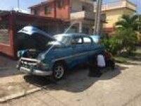 Cubanos consertam carro americano dos anos 50 no bairro Romerillo, em Havana