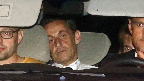Former French President Nicolas Sarkozy (C) arrives with police by car at the financial investigation unit in Paris to be presented to a judge late July 1, 2014. Former French President Sarkozy was held for questioning for 15 hours on Tuesday over suspicions he used his influence to secure leaked details of an inquiry into alleged irregularities in his 2007 election campaign. REUTERS/Pascal Rossignol (FRANCE - Tags: POLITICS CRIME LAW TPX IMAGES OF THE DAY)