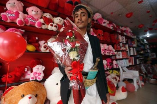 Rapaz compra buquê para celebrar o dia de São Valentim em Sanaa, capital do Iêmen.