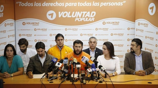 David Smolansky (C), opposition mayor of a district of Caracas, talks to the media next to Venezuelan opposition leader Maria Corina Machado (2nd R) during a news conference at the headquarters of political party Popular Will (Voluntad Popular) in Caracas June 5, 2014. Opposition leader Leopoldo Lopez, jailed in February for leading the protests, was being held in isolation in a military prison by the socialist government of President Nicolas Maduro, the International Commission of Jurists (ICJ) said. A judge in Caracas ruled on Thursday that Lopez should face trial on charges including instigating arson and damage in connection with the protests. REUTERS/Carlos Garcia Rawlins (VENEZUELA - Tags: POLITICS)