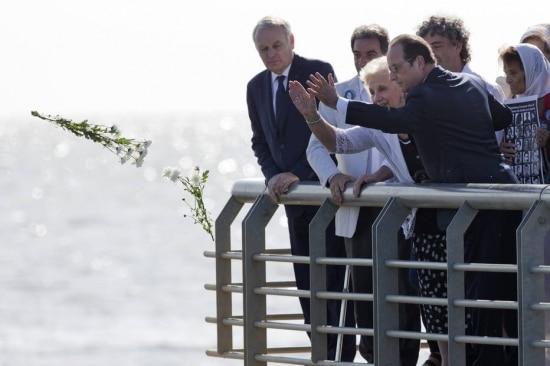 Hollande (D) e Estela de Carlotto, dirigente das Avós da Praça de Maio, lançam flores no Rio da Prata em homenagem às vítimas da ditadura