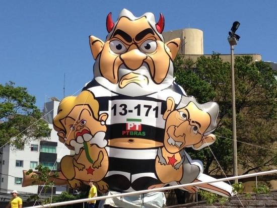 Nova versão do boneco inflável do ex-presidente Lula carrega, em uma das mãos uma representação de Dilma e, na outra, do governador de Minas gerais, Fernando Pimentel