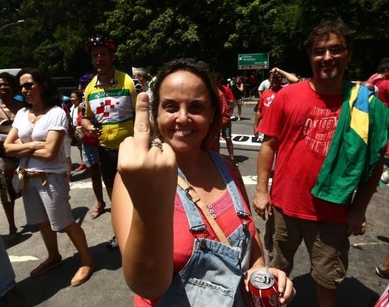 Lurian Lula da Silva, filha do ex-presidente Lula, mostra o dedo, dizendo que não fala com a mídia golpista