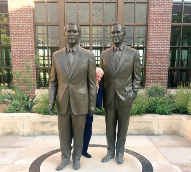 Bill Clinton sorrindo entre as estátuas