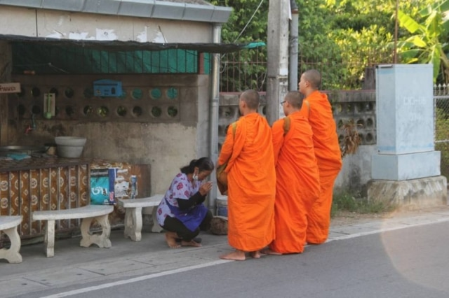 Comerciante dá alimentos e pede benção a monges em Chiang Mai