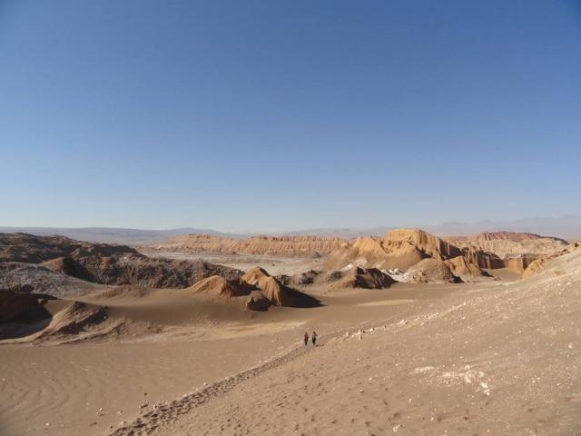 Turistas caminham pelo Vale da Lua, que deve ser um dos primeiros passeios do Atacama: paisagens que parecem de outro mundo e nenhum sinal de vegetação