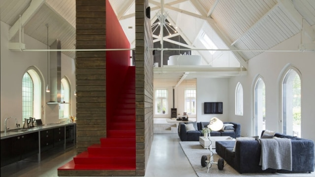A white interior of the former nave is punctuated by a red staircase to the master suite on the second floor in the church converted into a home by Ronald Olthof and his partner, Sofie Suiker, in Haarlo, Netherlands, May 30, 2014. The couple intended to convert an old factory into a home, but after a deal fell through, they ended up buying the church instead. (Andreas Meichsner/The New York Times)