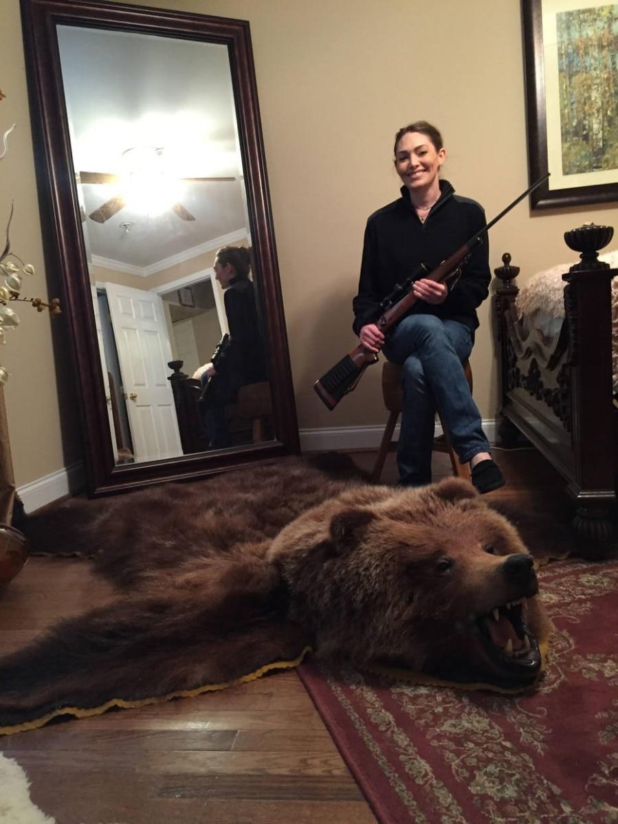 Hollie Sain e a pele do urso que ela matou em uma viagem ao Alasca; ela aprendeu a atirar na infância com o pai e agora ensina seu filho de 9 anos