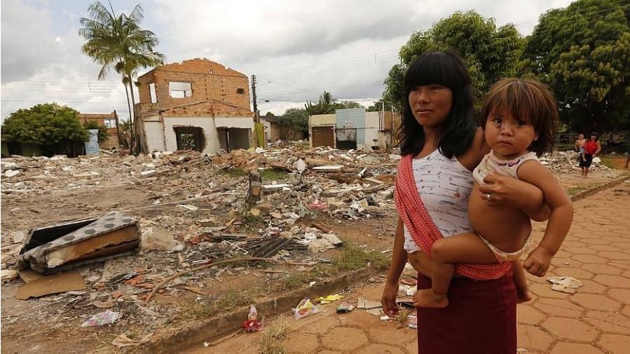 Indígenas passam ao lado de escombros em Altamira