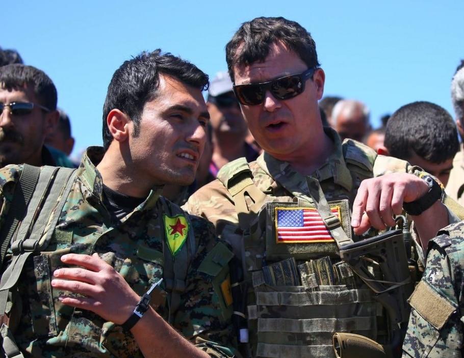 Soldado americano (D) conversa com combatente curdo das Unidades de Proteção do Povo (YPG) durante operação contra o Estado Islâmico na cidade síria de Derik - AFP PHOTO / DELIL SOULEIMAN