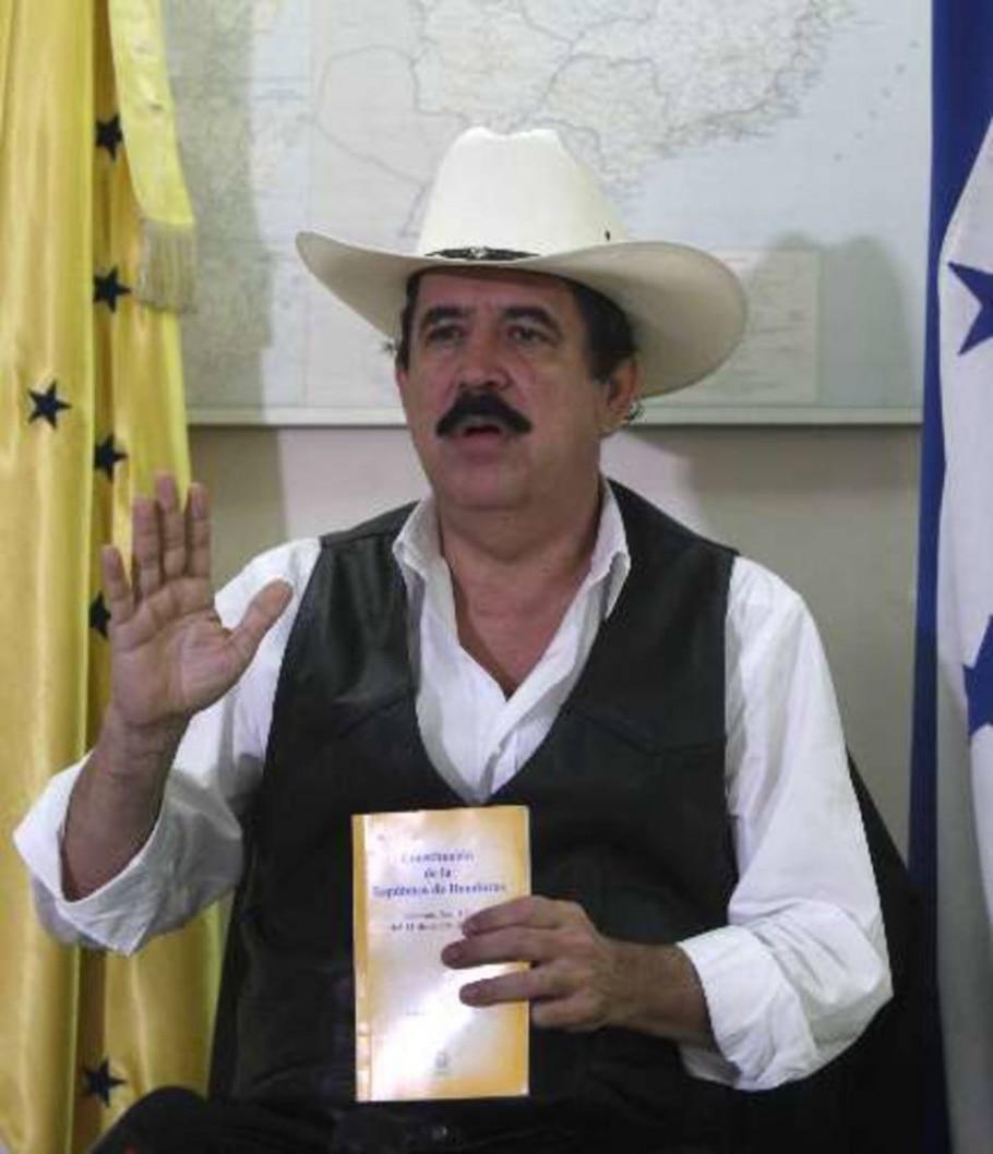 O líder deposto Manuel Zelaya discursa da embaixada brasileira com a Constituição nas mãos - Associated Press
