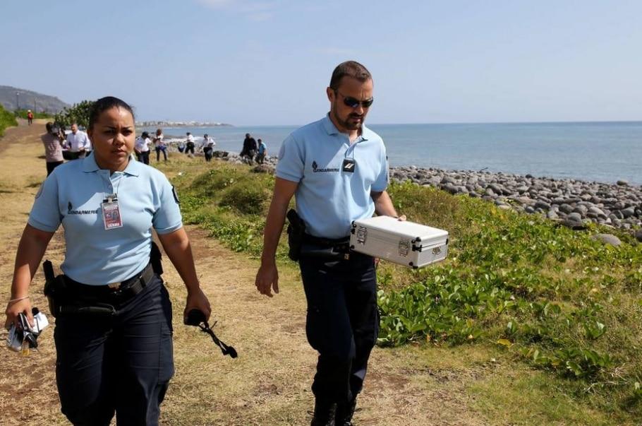 Policiais franceses da Ilha Reunião transportam objetos metálicos que podem ser partes de avião - AFP / Richard Bouhet
