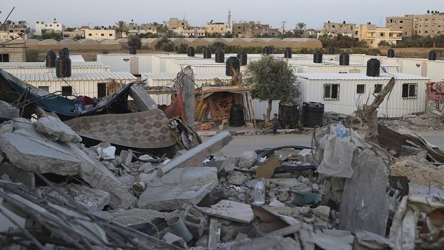 Destroços perto de contêineres que servem de abrigo a palestinos desalojados - Ibraheem Abu Mustafa/Reuters