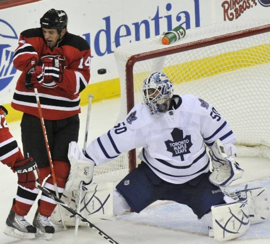 Sestito, do NJ Devils, desvia do disco, ao lado do goleiro Jonas Gustavsson, do Toronto Maple Leafs - Ray Stubblebine/Reuters - 26/12/2010