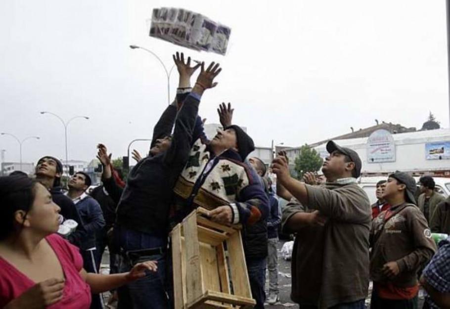 Chilenos disputam produtos saqueados em um supermercado de Concepción - Natacha Pisarenko/Associated Press