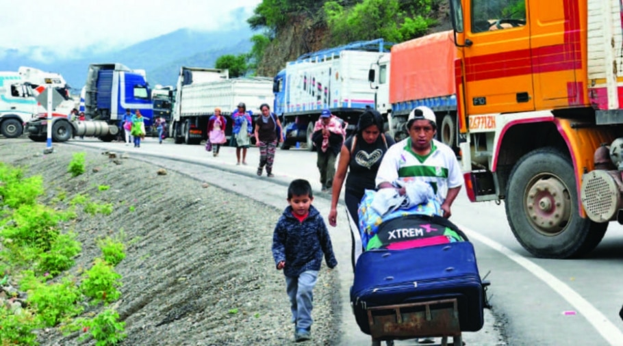 Bolivianos caminham nas margens de rodovia interditada por caminhoneiros - Reprodução / APG