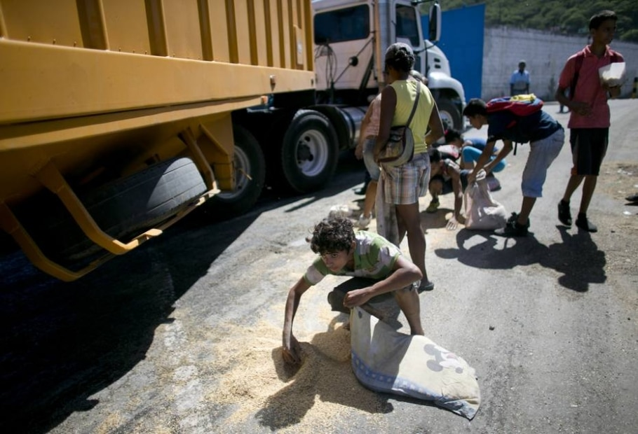 Venezuelanos coletam grãos de arroz que vazaram de caminhão nos arredores de Puerto Cabello; investigação da AP concluiu que militares controlam venda clandestina de alimentos no país - AP Photo/Ariana Cubillos