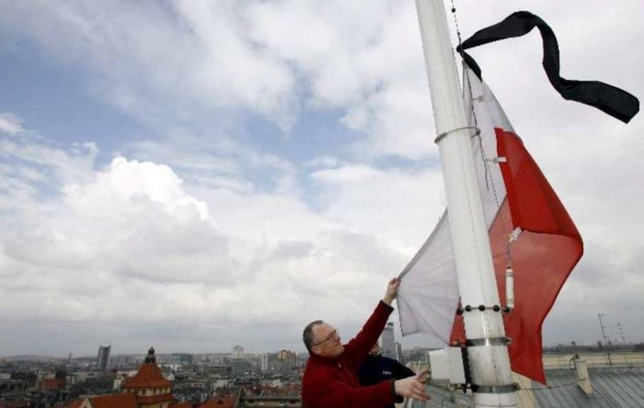 Homem hasteia bandeira e pano negro em luto pelas mortes do Presidente e pessoas do governo polonês - Andrzej Grygiel/EFE