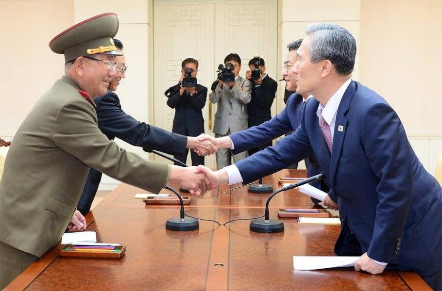 Representantes da Coreia do Norte (E) e da Coreia do Sul apertam as mãos após chegarem a acordo para reduzir tensão entre os países - REUTERS/the Unification Ministry/Yonhap